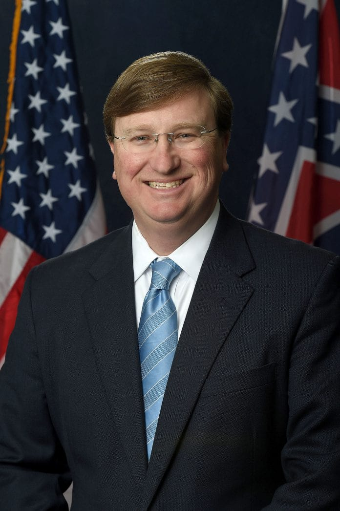 portrait of Mississippi governor Tate Reeves with US flag in background